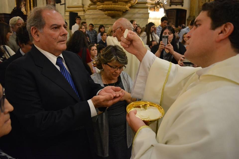 El nuevo sacerdote da la comunión a Rafael, su padre. A su lado está su madre, Graciela /C. Planelles
