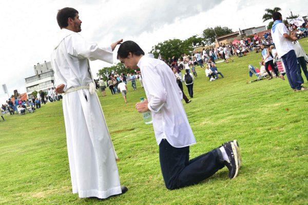 Un sacerdote imparte su bendición sobre un joven empapado antes del Gran Rosario/ Carlos Lebrato